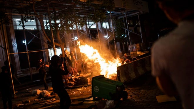 Protesters start fires along the SoHo shopping district on Sunday, May 31, 2020, in New York. Protests were held throughout the city over the death of George Floyd, a black man in police custody in Minneapolis who died after being restrained by police officers on Memorial Day.