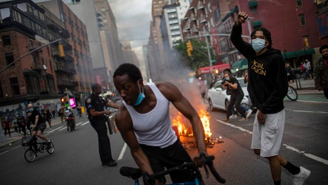 Protesters march down the street as trash burns in the background during a solidarity rally for George Floyd, Saturday, May 30, 2020, in New York. Protests were held throughout the city over the death of George Floyd, a black man who died after being restrained by Minneapolis police officers on May 25.