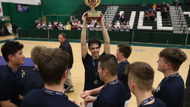 Patrick DiBartolo lifts the Section 9 Class D boys basketball trophy with his Livingston Manor teammates on Wednesday. The Wildcats defeated Chapel Field.