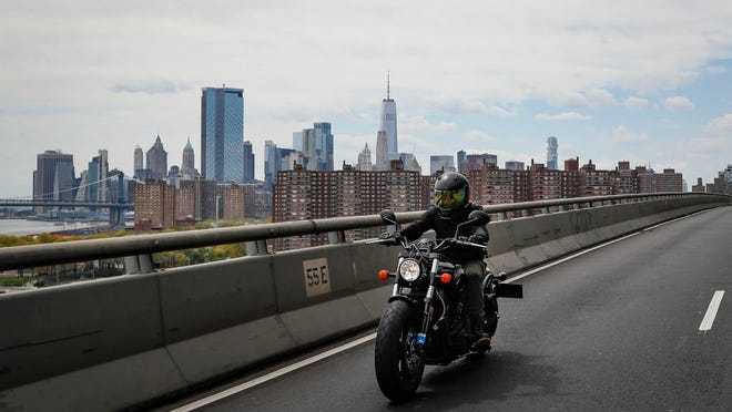 Ashley Zeolla rides her motorcycle over the Williamsburg Bridge on a delivery run of personal protective equipment to a doctors office with Masks for Docs as the lower Manhattan skyline looms in the distance Sunday, May 3, 2020, in New York.