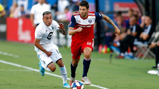 From Aug. 10, 2019, FC Dallas defender Ryan Hollingshead plays the ball while Minnesota United forward Miguel Ibarra chases him during the first half of an MLS soccer match in Frisco, Texas. Hollingshead has been sheltering in place since Major League Soccer suspended the season because of the coronavirus outbreak. But his experience has been a bit different than other athletes in the same situation. He and his family have spent the time bonding with their foster son.