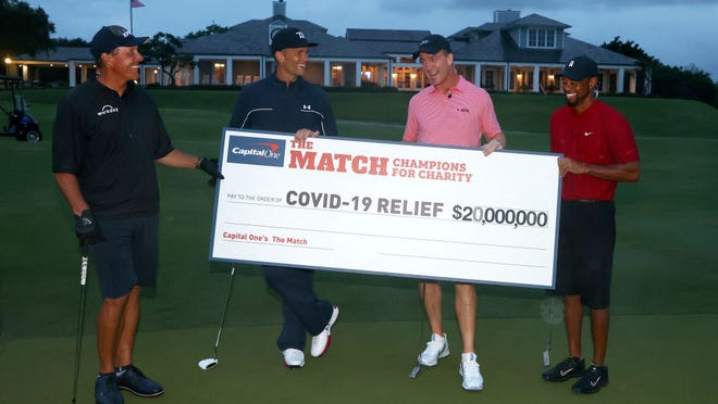 Phil Mickelson, Tom Brady, Peyton Manning and Tiger Woods hold a charity relief check worth $20 million following their Sunday match. TURNER SPORTS via TWITTER