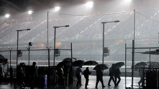 People leave the infield at Darlington Raceway after the NASCAR Xfinity series auto race was postponed because of rain Tuesday, May 19, 2020, in Darlington, S.C.
