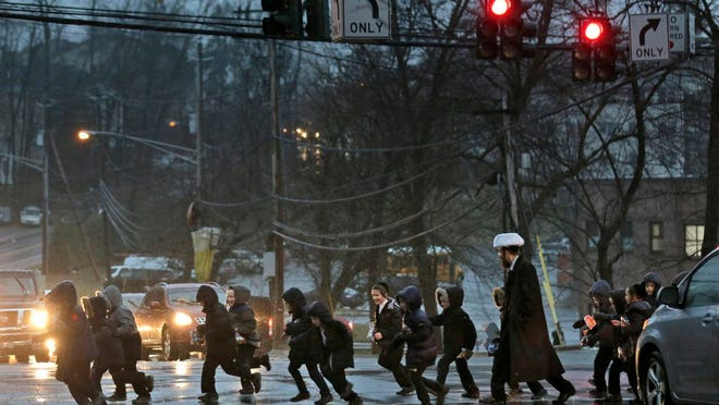 In this Monday, Dec. 30, 2019, photo, a group of orthodox Jewish children cross the street in Monsey, N.Y. The expansion of Orthodox Jewish communities in New York City's suburbs has led to sparring over new housing development and flare-ups of rhetoric that some say is cloaked anti-Semitism.