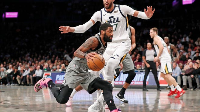 Brooklyn Nets guard Kyrie Irving (11) drives around Utah Jazz center Rudy Gobert (27) during the first quarter of an NBA basketball game Tuesday, Jan. 14, 2020, in New York.