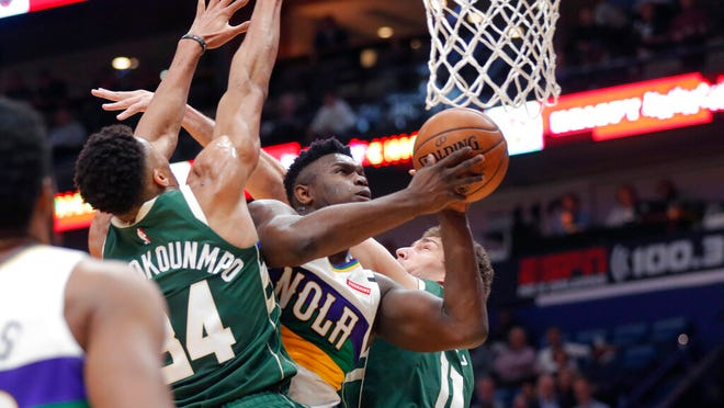 New Orleans Pelicans forward Zion Williamson goes to the basket between Milwaukee Bucks forward Giannis Antetokounmpo (34) and center Brook Lopez (11) in the first half of an NBA basketball game in New Orleans, Tuesday, Feb. 4, 2020.