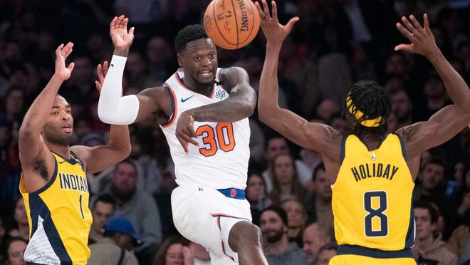 New York Knicks forward Julius Randle (30) moves the ball around Indiana Pacers forwards Justin Holiday (8) and T.J. Warren (1) in the first half of an NBA basketball game, Friday, Feb. 21, 2020, at Madison Square Garden in New York.