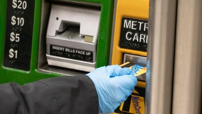 "A woman wears a protective glove as she purchases a metro card at a subway station, Wednesday, March 4, 2020, in New York. She said that she always wears gloves in the subway ""because it's filthy."" According to the Centers for Disease Control and Prevention, (CDC), ""It may be possible that a person can get COVID-19 by touching a surface or object that has the virus on it and then touching their own mouth, nose, or possibly their eyes, but this is not thought to be the main way the virus spreads."""
