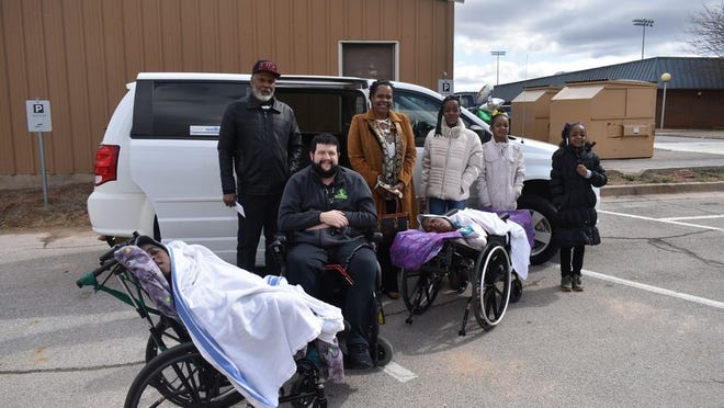 From left to right Dashon Caldwell Jones, Ben Simpson, Rufus Caldwell Jones, Felicia Caldwell Jones, Shabree Caldwell Jones, Leaja Caldwell Jones, Amynah Caldwell Jones and Nyelay Caldwell Jones in front of the handicap accessible van the Ben Strong Foundation donated to the family Wednesday in Shawnee.