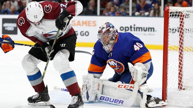 Colorado Avalanche right wing Joonas Donskoi (72) tries to get oriented with the puck as New York Islanders goaltender Semyon Varlamov (40) defends the crease during the first period of an NHL hockey game, Monday, Jan. 6, 2020, in Uniondale, N.Y.