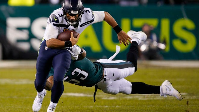Seattle Seahawks' Russell Wilson (3) rushes past Philadelphia Eagles' Nigel Bradham (53) during the second half of an NFL wild-card playoff football game, Sunday, Jan. 5, 2020, in Philadelphia.
