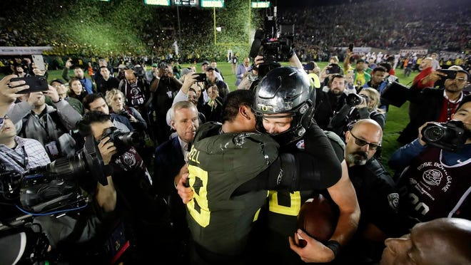 Oregon quarterback Justin Herbert, right, hugs offensive lineman Penei Sewell after their win against Wisconsin in the Rose Bowl.