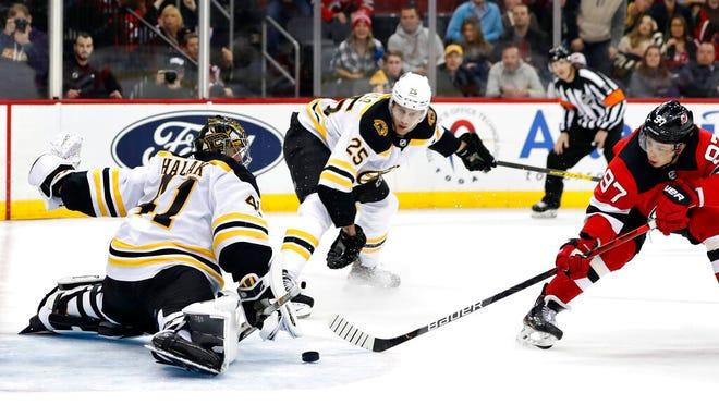 New Jersey Devils left wing Nikita Gusev (97) tries to get a shot past Boston Bruins goaltender Jaroslav Halak (41) as Bruins defenseman Brandon Carlo (25) looks on during the second period of an NHL hockey game, Tuesday, Dec. 31, 2019, in Newark, N.J.
