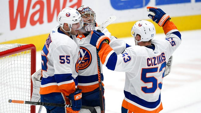 New York Islanders center Casey Cizikas (53), defenseman Johnny Boychuk (55) and goaltender Semyon Varlamov (40) celebrate after an NHL hockey game against the Washington Capitals, Tuesday, Dec. 31, 2019, in Washington. The Islanders won 4-3.