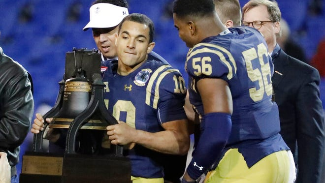 Navy quarterback Malcolm Perry (10) holds the trophy after Navy beat Kansas State in the Liberty Bowl NCAA college football game Tuesday, Dec. 31, 2019, in Memphis, Tenn. Navy won 20-17.