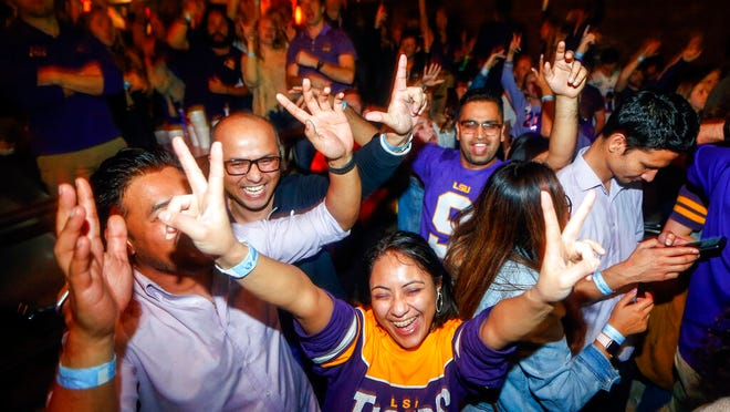 LSU fans celebrate at Varsity Theatre, in Baton Rouge, La., after LSU defeated Clemson 42-25 in the NCAA College Football Playoff championship game, Monday, Jan. 13, 2020.
