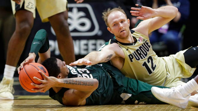Purdue forward Evan Boudreaux (12) defends against Michigan State forward Xavier Tillman (23) on the floor during the second half of an NCAA college basketball game in West Lafayette, Ind., Sunday, Jan. 12, 2020.