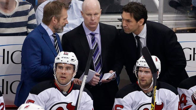 New Jersey Devils head coach John Hynes, center, confers with assistants, Geoff Ward, left, and Alain Nasreddine during an NHL hockey game against the Pittsburgh Penguins in Pittsburgh, Thursday, March 24, 2016.