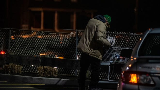 A homeless man takes his belongings out of his shopping cart in the McDonald's parking lot in the City of Newburgh on Wednesday. Homelessness appears to be on the increase in Newburgh.