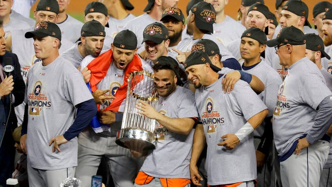 From Nov. 1, 2017, the Houston Astros celebrate with the trophy after their win against the Los Angeles Dodgers in Game 7 of baseball's World Series in Los Angeles. The Los Angeles City Council wants Major League Baseball to strip the Houston Astros and Boston Red Sox of their World Series titles and award the trophies to the Dodgers. The resolution was introduced Tuesday, Jan. 21, 2020, after it was revealed that the Astros used a system by then-coach Alex Cora in 2017 to tip off batters on what pitch was to be thrown.