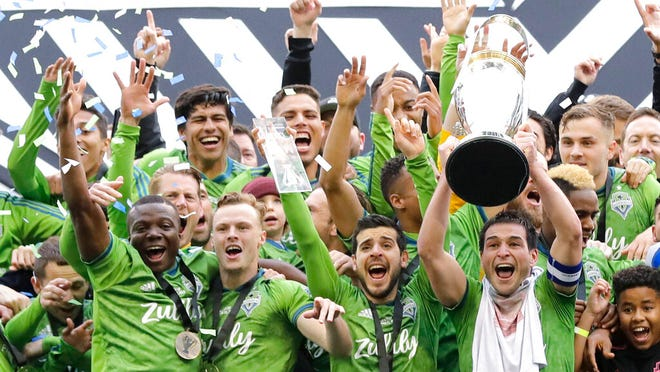 From Nov. 10, 2019, Seattle Sounders captain Nicolas Lodeiro, right, lifts the MLS Cup trophy as he celebrates with teammates after the Sounders defeated Toronto FC in the MLS Cup championship soccer match in Seattle. Major League Soccer and its players have reached a new five-year collective bargaining agreement in time for the start of the season. The new contract must be approved by the MLS Board of Governors and the membership of the Major League Soccer Players Association.