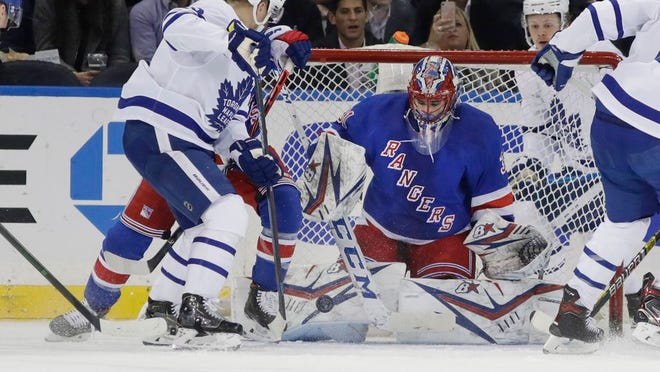 Rangers goaltender Igor Shesterkin (31) stops a shot on goal by Toronto Maple Leafs' Andreas Johnsso, left, during the second period.