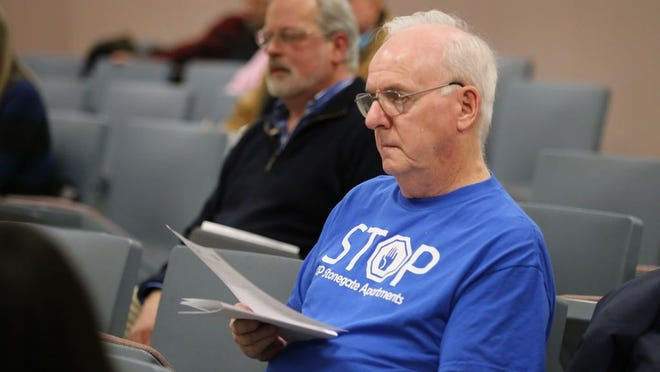 "New Windsor resident Donald Coyle sits in the audience at Wednesday's Town Board meeting wearing a shirt that reads ""Stop Stonegate Apartments,"" which is a 310-unit apartment project."