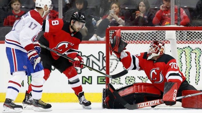 New Jersey Devils goaltender Louis Domingue (70) makes a save during the second period of the team's NHL hockey game against the Montreal Canadiens, Tuesday, Feb. 4, 2020, in Newark, N.J. Canadiens left wing Ilya Kovalchuk (17) and Devils defenseman Will Butcher watch.