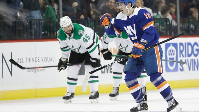 New York Islanders' Mathew Barzal (13) celebrates after scoring a goal during the third period of an NHL hockey game as he passes Dallas Stars' Roman Polak (45) Tuesday, Feb. 4, 2020, in New York. The Islanders won 4-3.