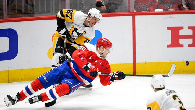 Washington Capitals center Lars Eller (20), of Denmark, falls to the ice next to Pittsburgh Penguins center Sidney Crosby (87) during the third period of an NHL hockey game, Sunday, Feb. 2, 2020, in Washington.