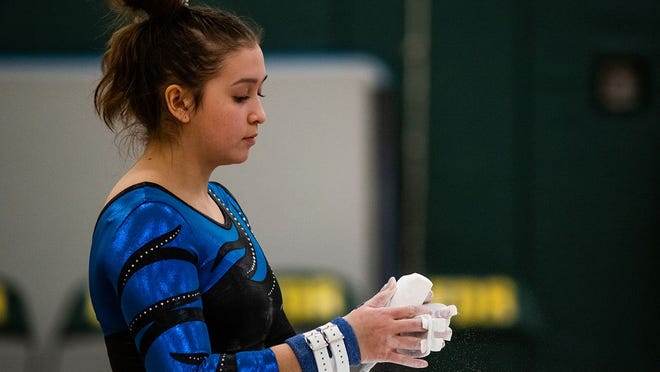 Wallkill's Liliyanne Shearer chalks up her hands before competing on the uneven bars during the Section 9 gymnastics championships at FDR High School in Hyde Park, NY on Wednesday, February 19th, 2020. KELLY MARSH/FOR THE TIMES HERALD-RECORD