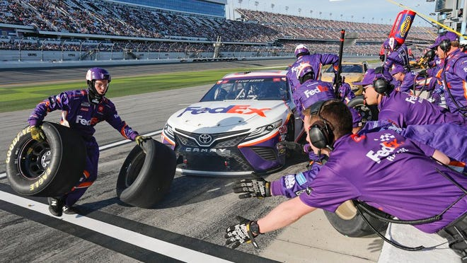 Denny Hamlin's crew changes tires and refuels during a pit stop during the NASCAR Daytona 500 auto race at Daytona International Speedway, Monday, Feb. 17, 2020, in Daytona Beach, Fla. Sunday's race was postponed sue to rain.