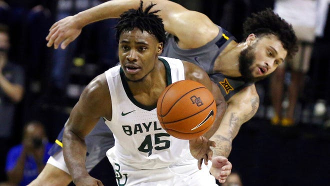 Baylor guard Davion Mitchell, left, breaks away from West Virginia guard Jermaine Haley for a fast break in the second half of an NCAA college basketball game, Saturday, Feb. 15, 2020, in Waco, Texas.