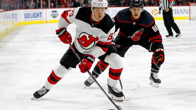 New Jersey Devils' Jesper Bratt (63), of Sweden, protects the puck from Carolina Hurricanes' Teuvo Teravainen (86), of Finland, during the first period of an NHL hockey game in Raleigh, N.C., Friday, Feb. 14, 2020.
