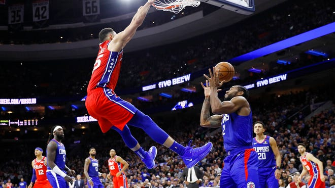 Philadelphia 76ers' Ben Simmons, left, dunks the ball against Los Angeles Clippers' Kawhi Leonard during the second half of an NBA basketball game, Tuesday, Feb. 11, 2020, in Philadelphia.