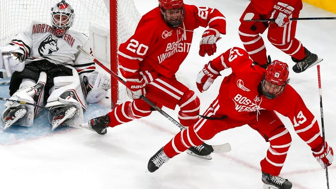 Boston University's Trevor Zegras (13) celebrates his tying goal against Northeastern's Craig Pantano, left, during the third period of the Beanpot Tournament championship NCAA college hockey game in Boston, Monday, Feb. 10, 2020.