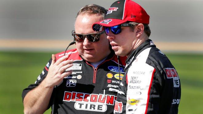 Brad Keselowski, right, talks with a crew member on pit road during NASCAR auto race qualifying at Daytona International Speedway, Sunday, Feb. 9, 2020, in Daytona Beach, Fla.