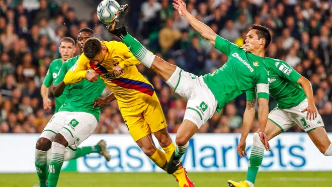 Barcelona's Clement Lenglet, left, and Betis' Aissa Mandi in action during La Liga soccer match between Betis and Barcelona at the Benito Villamarin stadium in Seville, Spain, Sunday, Feb. 9, 2020.