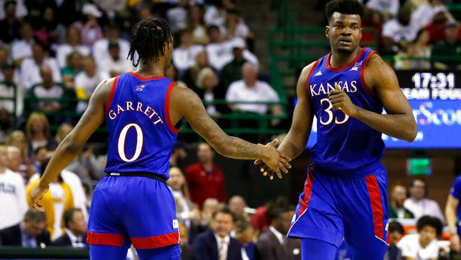Kansas center Udoka Azubuike, right, low fives guard Marcus Garrett, left, after a made basket against Baylor during the second half of an NCAA college basketball game on Saturday, Feb. 22, 2020, in Waco, Texas.