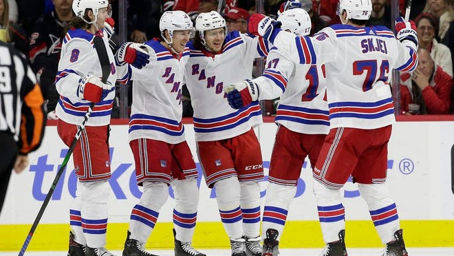 New York Rangers defenseman Jacob Trouba (8), from left, center Ryan Strome, left wing Artemi Panarin, of Russia, right wing Jesper Fast (17), of Sweden, and defenseman Brady Skjei (76) celebrate after Fast scored a goal against the Carolina Hurricanes during the second period of an NHL hockey game in Raleigh, N.C., Friday, Feb. 21, 2020.
