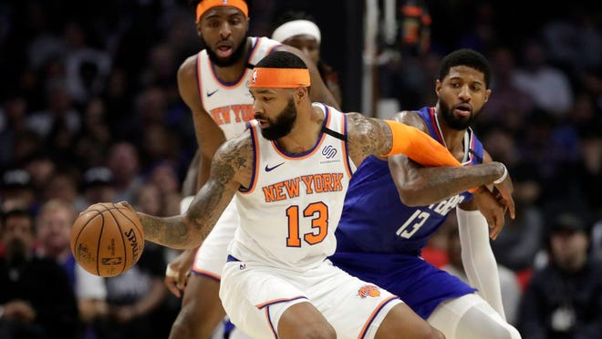 New York Knicks' Marcus Morris Sr., front left, is defended by Los Angeles Clippers' Paul George, right, during the first half of an NBA basketball game Sunday, Jan. 5, 2020, in Los Angeles.