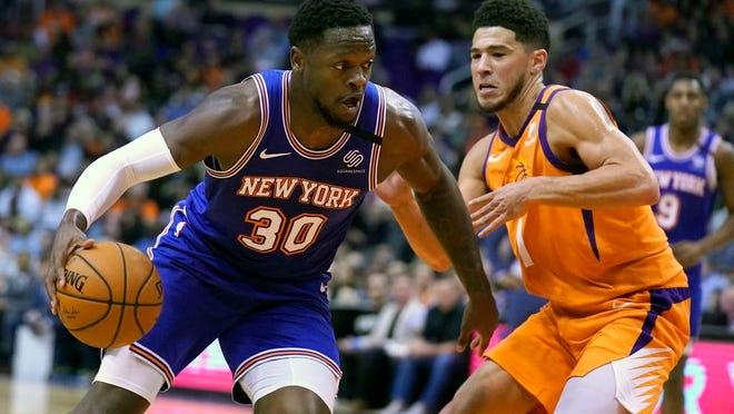 Knicks forward Julius Randle drives against Phoenix Suns guard Devin Booker.