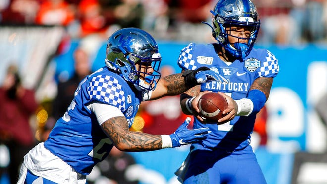 Kentucky quarterback Lynn Bowden Jr. hands off to running back Christopher Rodriguez Jr. who rushes for a touchdown against Virginia Tech in the first half of the Belk Bowl NCAA college football game in Charlotte, N.C., Tuesday, Dec. 31, 2019.