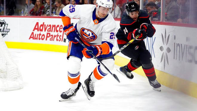New York Islanders' Brock Nelson (29) moves the puck away from a charging Carolina Hurricanes' Justin Williams (14) during the second period of an NHL hockey game in Raleigh, N.C., Sunday, Jan. 19, 2020.