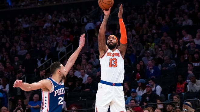 New York Knicks forward Marcus Morris Sr. (13) shoots a three-point basket past Philadelphia 76ers guard Ben Simmons (25) in the second half of an NBA basketball game, Saturday, Jan. 18, 2020, at Madison Square Garden in New York.