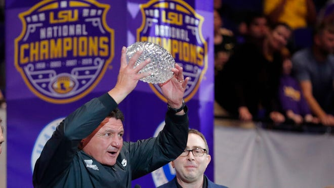 LSU head coach Ed Orgeron holds up the American Football Coaches Association National Championship Trophy during a celebration of their NCAA college football championship, Saturday, Jan. 18, 2020, on the LSU campus in Baton Rouge, La.