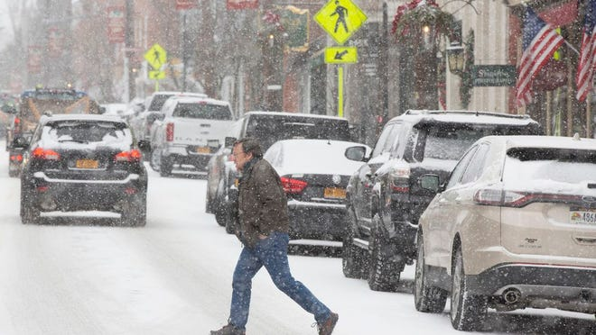 A pedestrian crosses Main Street in Warwick as it begins to snow on Saturday afternoon.