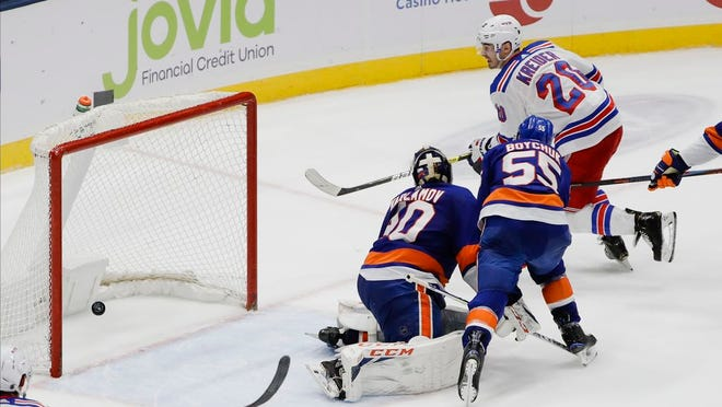 New York Rangers' Chris Kreider (20) shoots the puck past New York Islanders goaltender Semyon Varlamov (40) and Johnny Boychuk (55) for the game winning goal during the third period of an NHL hockey game Thursday, Jan. 16, 2020, in Uniondale, N.Y. The Rangers won 3-2.