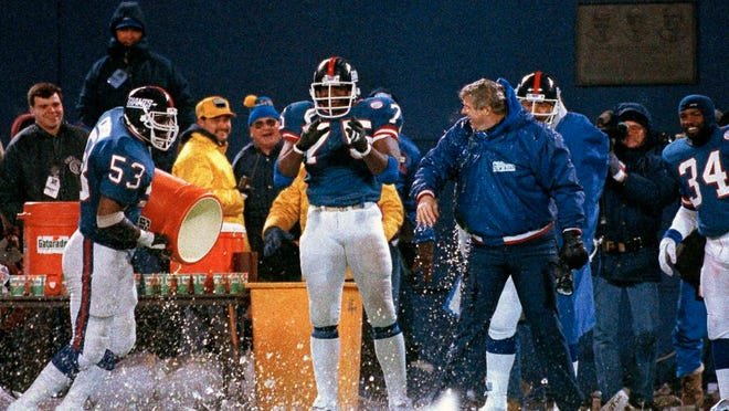 FILE - In this Jan. 11, 1987, file photo, New York Giants George Martin (75) watches as teammate Harry Carson empties the water bucket on coach Bill Parcells during the last minute of their 17-0 win over the Washington Redskins in the NFC championship in East Rutherford, N.J. Teams are never supposed to choose to kick off after winning the coin toss because it means they won't get the ball to start either half. But games rarely have wind gusts of 25 mph and beyond. That was the case when the Giants beat the Redskins 17-0 for the 1986 NFC title.
