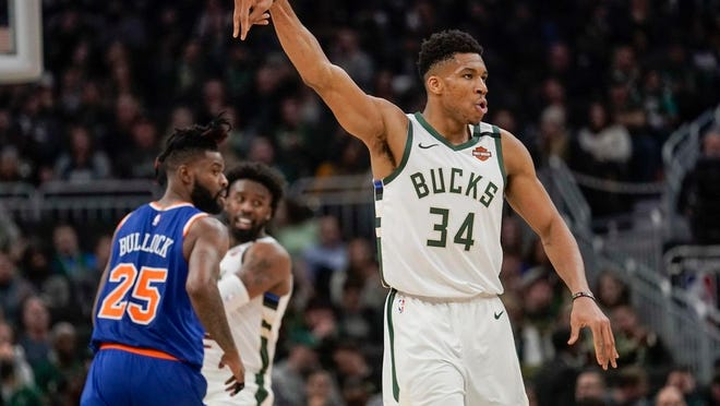 Milwaukee Bucks' Giannis Antetokounmpo reacts to his three-point basket during the second half of an NBA basketball game against the New York Knicks Tuesday, Jan. 14, 2020, in Milwaukee.